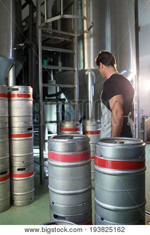 Side view of worker standing by vats and kegs at warehouse