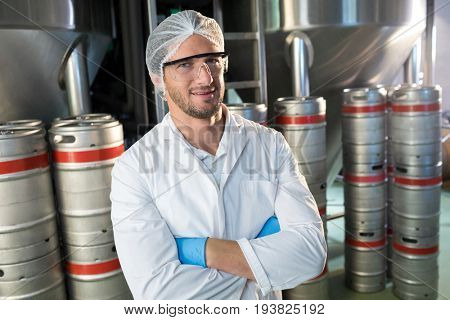 Portrait of worker in uniform standing by kegs at warehouse
