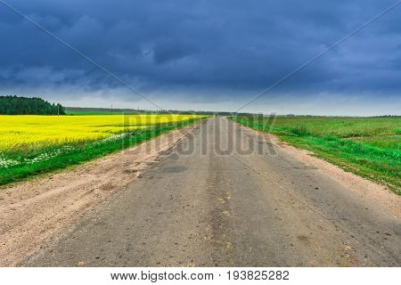 Rural Road Merges With The Horizon, Overcast Sky, Belarus Summer