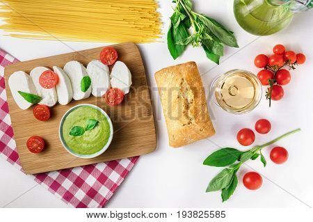 Overhead photo of an assortment of Italian foods on white background with copy space. Buffalo mozzarella cheese, cherry tomatoes, basil leaves, pesto sauce, spaghetti pasta, olive oil, ciabatta bread