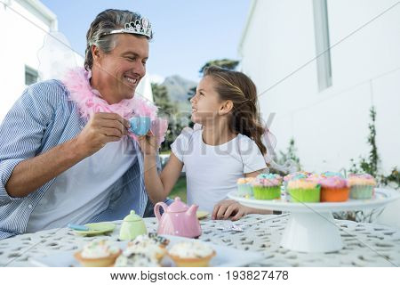 Smiling father and daughter in fairy costume toasting cup of tea at garden