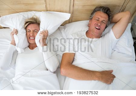 Annoyed woman covering ears with pillow while man snoring on bed in bedroom