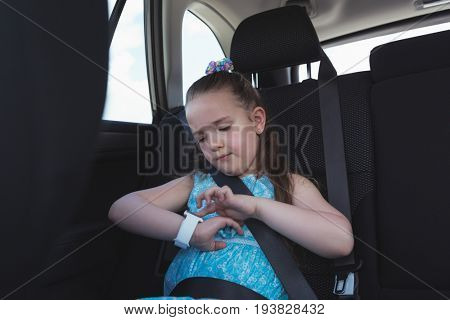 Cute girl adjusting smart watch in car