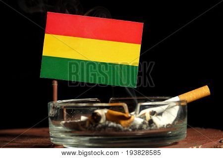 Bolivian Flag With Burning Cigarette In Ashtray Isolated On Black Background