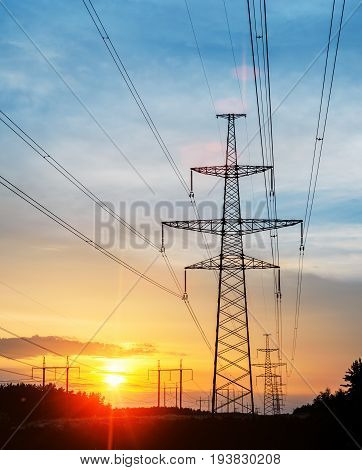 Electricity pylons and power lines at sunset