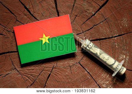 Burkina Faso Flag On A Stump With Syringe Injecting Money In Flag