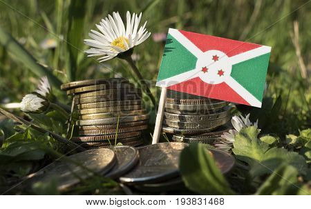 Burundi Flag With Stack Of Money Coins With Grass And Flowers