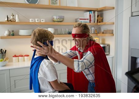 Mother and son pretending to be superhero in the kitchen at home