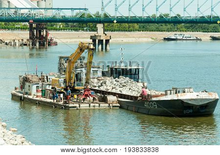 Two cargo barge with lifting dredge transport junk of rock from bridge construction site on Danube river. July - 04. 2017. Novi Sad, Serbia.