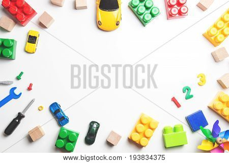 Kids toys frame with construction blocks, cubes, toy tools and cars on white background. Top view. Flat lay.