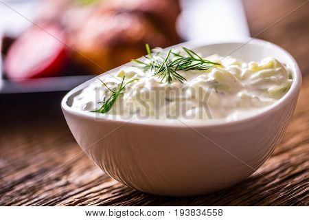 Tzatziki. Tzatziki sauce dip or dressing with chicken grill legs in the background.