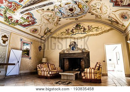 TORRE ALFINA, ITALY. November 8, 2015: Extraordinary reception room inside the castle of Torre Alfina, Italy. Vaulted ceiling painted. Fireplace, sofas, armchairs historical. Century historic hall.