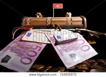 Montenegrin Flag On Top Of Crate Full Of Money