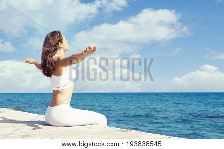 Young and beautiful girl in white sportswear doing yoga on a wooden pier at summer. Yoga, sport, leisure, vacation and traveling concept.