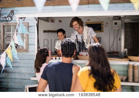 Smiling waiter giving order to customer at counter in food truck van