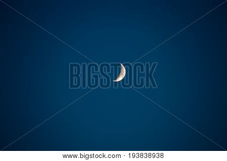 A young moon on a clear blue sky in the darkness of darkness