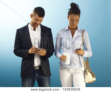 Young couple using mobilephone over blue background.