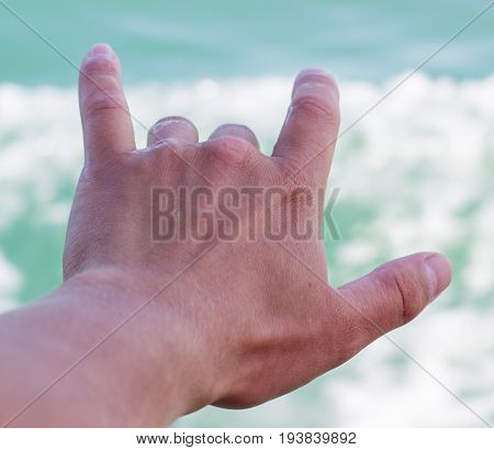 Gesture of coolness on the background of the sea hand on a background of clear sea water