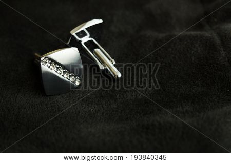 Silver cufflinks with rhinestones for men's shirts on a black background on the left