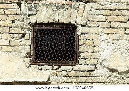 Basement window with rusty iron bars on old abandoned brick house.