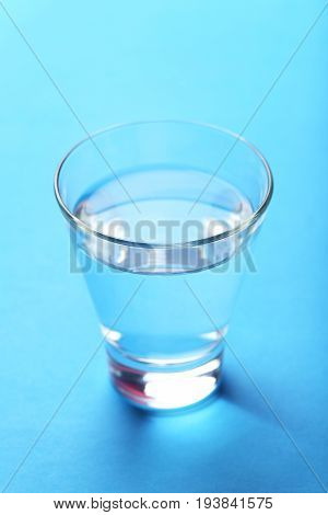 Glass with water on the blue background