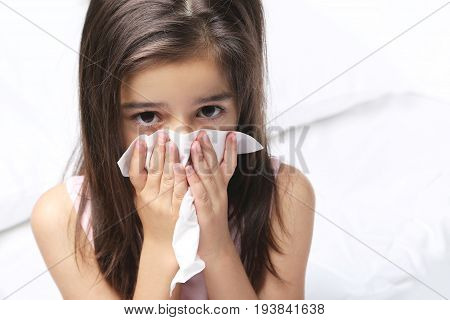 Beautiful little girl with handkerchief on white bed