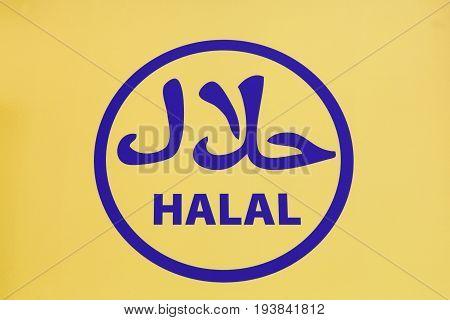 Halal food sign on a yellow wall