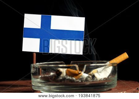 Finnish Flag With Burning Cigarette In Ashtray Isolated On Black Background