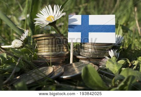 Finnish Flag With Stack Of Money Coins With Grass And Flowers