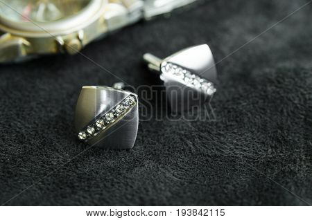 Silver cufflinks with crystals lie on a black cloth next to the watches the cufflinks catches the light