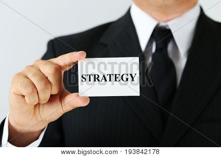 Businessman holding card with the word Strategy