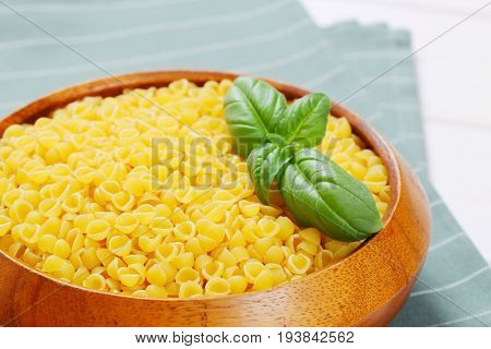 bowl of small pasta shells on grey place mat - close up