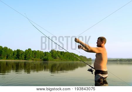 fisherman fishing in a calm river in the morning. Man in fishing gear stending in a river and throws a fishing pole.