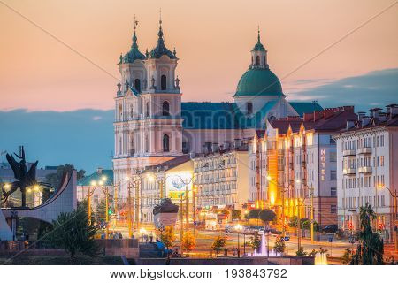 Grodno, Belarus - June 9, 2017: Part Of Grodno Regional Drama Theatre, St. Francis Xavier Cathedral And Traffic In Mostowaja And Kirova Streets At Evening In Night Illuminations Lights. Sunset Sky