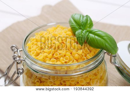 jar of small pasta shells on beige place mat - close up