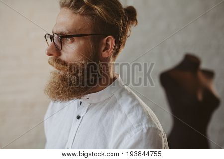 Man wearing glasses and thick beard standing in tailors workshop with pensive look.