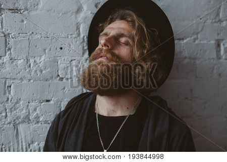 Young man with thick beard with closed eyes wearing black hat daydreaming next to white brick wall.