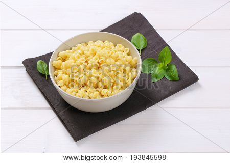 bowl of small pasta shells on dark grey place mat