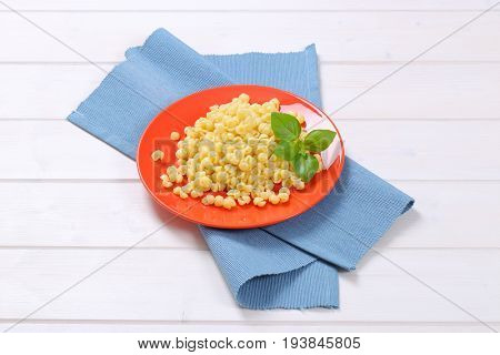 plate of small pasta shells on blue place mat