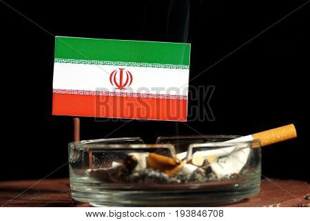 Iranian Flag With Burning Cigarette In Ashtray Isolated On Black Background