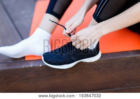 Athlete ties shoelaces on sneaker in gym, sitting on rug on the wooden floor