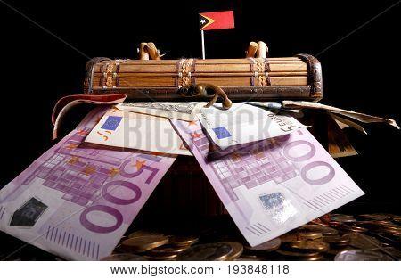 East Timor Flag On Top Of Crate Full Of Money