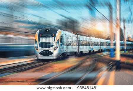 High speed commuter train at the railway station at sunset in Europe. Modern intercity train on railway platform. Urban view with beautiful passenger train on railroad track. Railway transportation