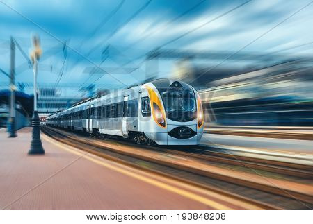 High speed train at the railway station at sunset in Europe. Modern intercity train on railway platform. Urban view with beautiful passenger train on railroad and buildings. Railway transportation