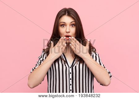 Young girl in striped shirt holding hands on mouth looking interested on pink background.
