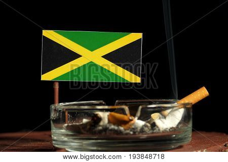 Jamaican Flag With Burning Cigarette In Ashtray Isolated On Black Background