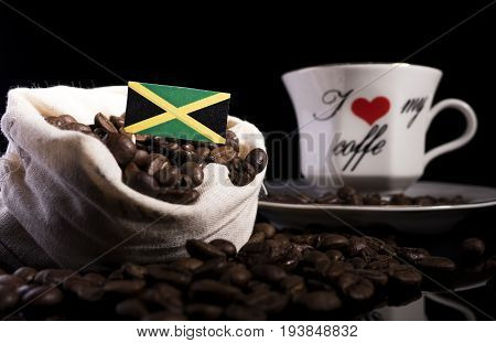 Jamaican Flag In A Bag With Coffee Beans Isolated On Black Background