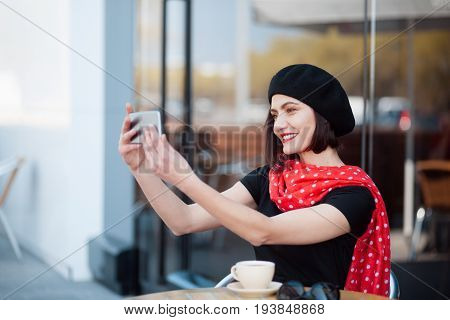 Adult elegant woman n beret sitting with coffee outside and taking selfie.