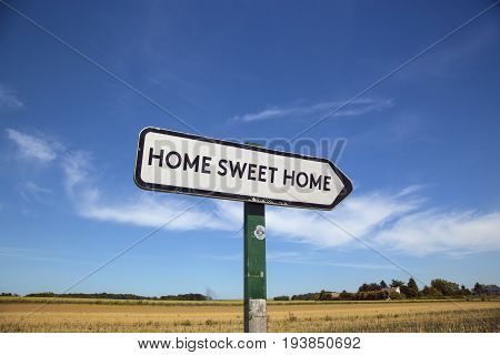 In the countryside a road sign with the inscription home sweet home with a blue sky and a field in the background