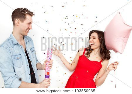 Girl in red dress with balloon laughing while man bursting party popper on white background.